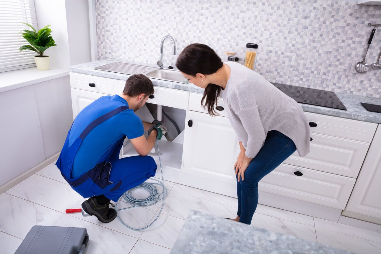 Woman watching plumber fix pipes under sink